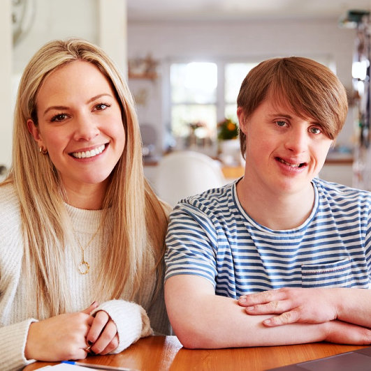 a caregiver and a person with down syndrome smiling