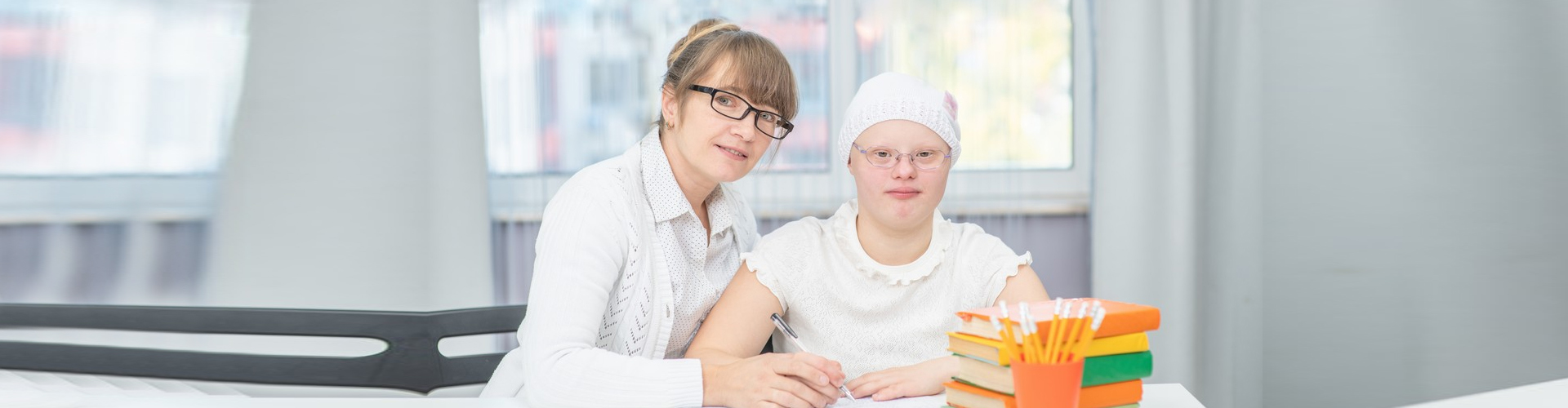 Portrait of happy teacher and girl with Down Syndrome at school