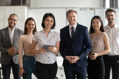 Diverse professional business leaders posing with multicultural workers in office