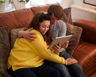A person with down syndrome using digital tablet at home with his caregiver