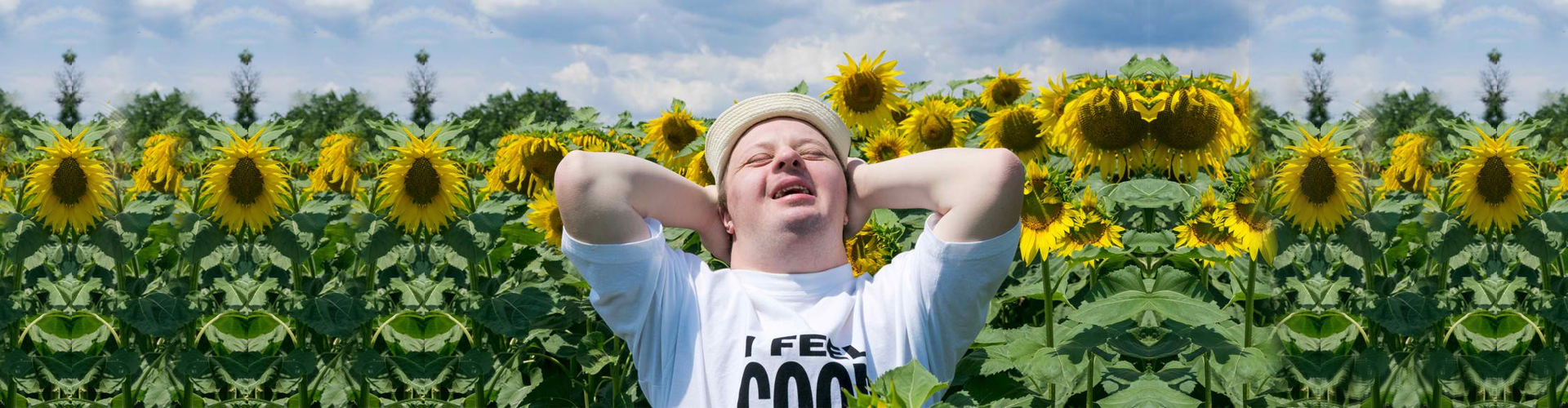 Happy young man with down syndrome relaxing in the sunflower field