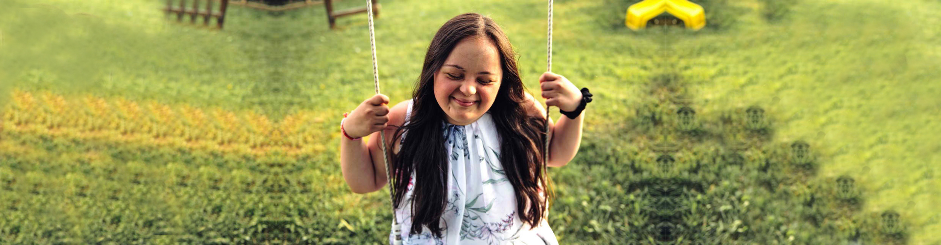 a picture of an adult girl with down syndrome outside at sunset